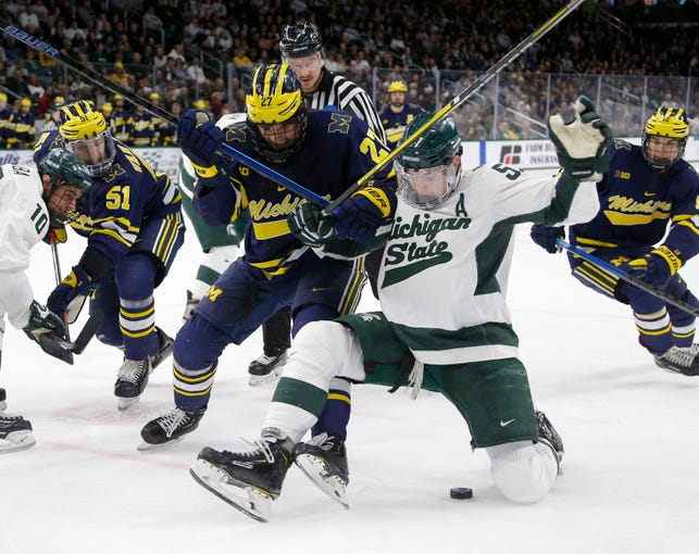 Michigan State's Jerad Rosburg, right, and Michigan's Nolan Moyle battle for the puck during the second period, Saturday, Nov. 16, 2019, in East Lansing, Mich. Michigan State won 3-0.
