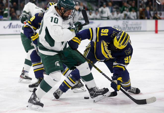 Michigan State's Sam Saliba, left, and Michigan's Nick Pastujov (91) battle for the puck in a game earlier this season.