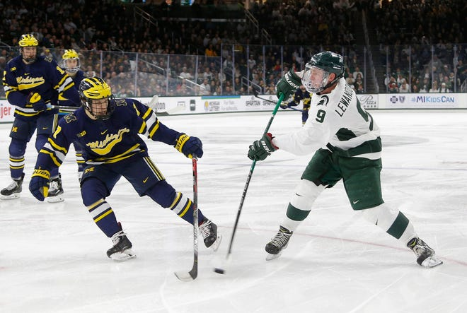 Michigan State's Mitchell Lewandowski, right, shoots against Michigan's Johnny Beecher during the third period, Saturday, Nov. 16, 2019, in East Lansing, Mich. Michigan State won 3-0.