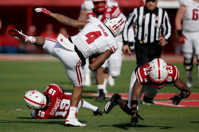 Wisconsin wide receiver A.J. Taylor starts to regain his balance after bouncing off a pair of Nebraska defenders during his 55-yard touchdown reception in the second quarter.