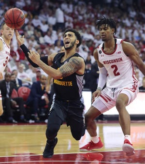 Marquette guard Markus Howard  is fouled by Wisconsin's  Aleem Ford on his way to the basket Saturday at the Kohl Center.