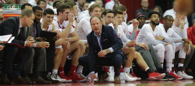 Wisconsin head coach Greg Gard talks with his staff during the first half.