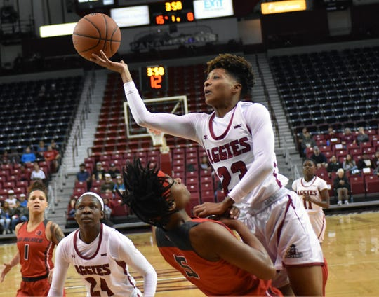 New Mexico State guard Aaliyah Prince goes over a UNM Lobo defender for a shot as the Aggies took on the Lobos on Sunday afternoon.