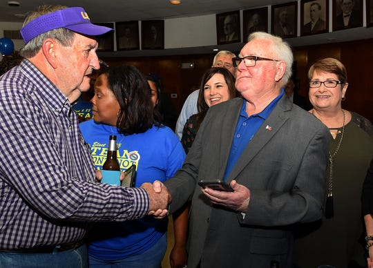 Bill Fontenot receives congratulations from Armand Castille.