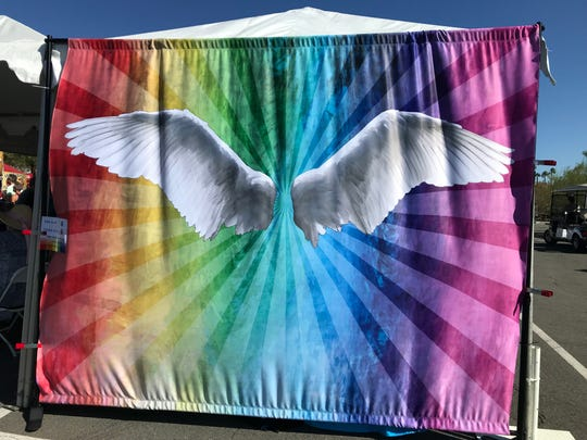 Attendees took photos in front of the angel wings with a rainbow background.