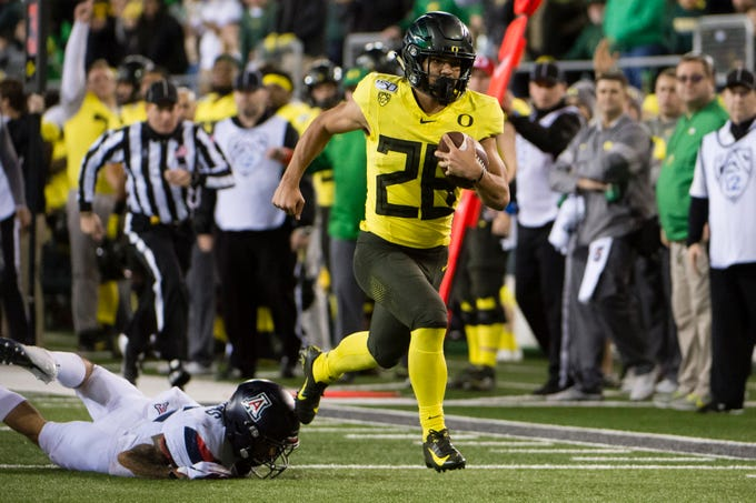 Nov 16, 2019; Eugene, OR, USA; Oregon Ducks running back Travis Dye (26) breaks away from a Arizona Wildcats defender for a touchdown during the second half at Autzen Stadium. Mandatory Credit: Troy Wayrynen-USA TODAY Sports