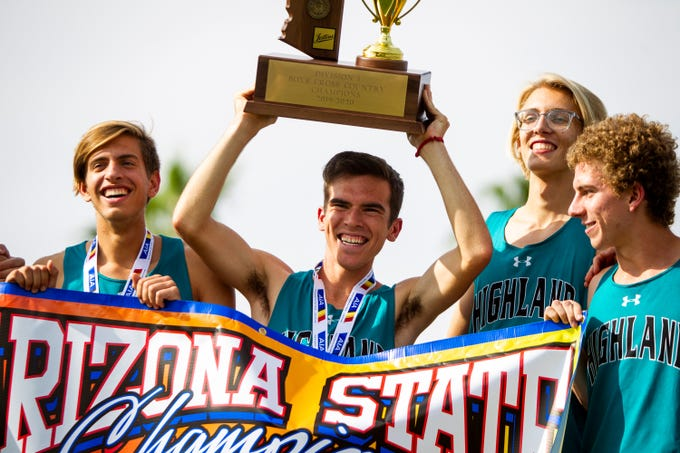 The Highland boys team raises their Division 1 state championship trophy during the state cross-country championships at Cave Creek Golf Course in Phoenix on Saturday, Nov. 16, 2019.