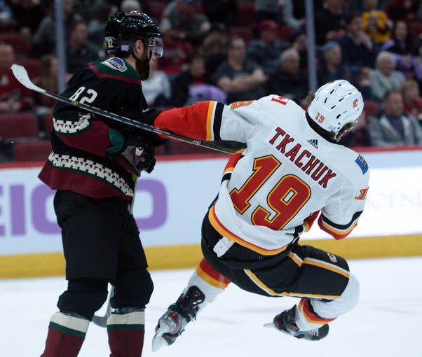 Nov 16, 2019; Glendale, AZ, USA; Arizona Coyotes defenseman Jordan Oesterle (82) checks Calgary Flames left wing Matthew Tkachuk (19) during the third period at Gila River Arena.