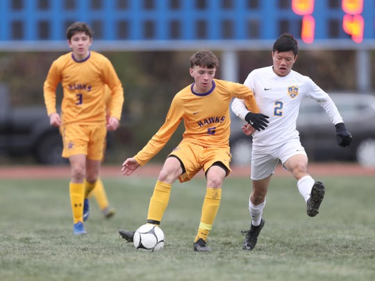 Rhinebeck's Jonathan Lange (5) and Lansing's Morgan Somchanhnovong (2) battle for possession during the NYSPHSAA boys Class C state soccer final at Middletown High School on Sunday, November 17, 2019.