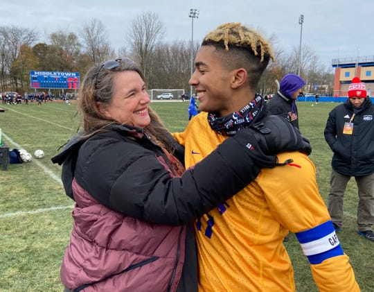 Sascha Zuger hugs her son, Nakoa, as Rhinebeck celebrates winning a boys soccer state championship. Sascha Zuger had rushed back from work in Antigua to watch the game in person.
