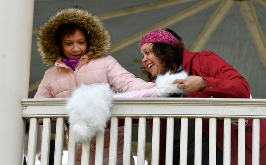 Aaliyah Cooper, 12, and mom Michelle of Mount Wolf tie some of the hundreds of donated scarves, hats, jackets, blankets and more around the band shell at Farquhar Park for the homeless and less fortunate, Sunday, November 17, 2019.John A. Pavoncello photo