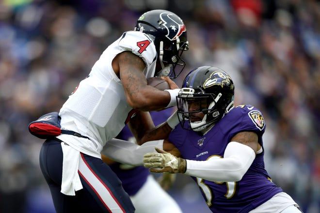 Houston Texans quarterback Deshaun Watson, left, runs with the ball as Baltimore Ravens cornerback Brandon Carr makes the tackle during the first half of an NFL football game, Sunday, Nov. 17, 2019, in Baltimore. (AP Photo/Gail Burton)