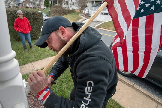 Adam Jacoby, right, installs a flag for Shirley Puente on Manchester Street in Glen Rock.