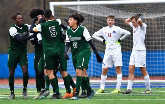 Fairport's Timmy Hirschler, right, and Kevin Clifford look on as Brentwood celebrates its second goal during the NYSPHSAA Boys Soccer Class AA championship Sunday, Nov. 17, 2019 in Middletown. Fairport's season ended with a 4-0 loss to Brentwood-XI.
