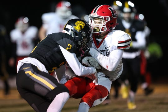 Lancaster's Shawn Davis (3) is tackled by McQuaid's Sam Perozzi (2) during the Knights 32-28 win on Saturday night in the Class AA Far West regional game.