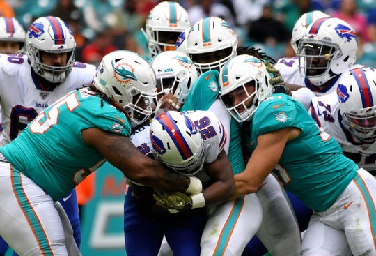 Buffalo Bills running back Devin Singletary (26) is tackled by Miami Dolphins defensive tackle John Jenkins (95) during the first half at Hard Rock Stadium.