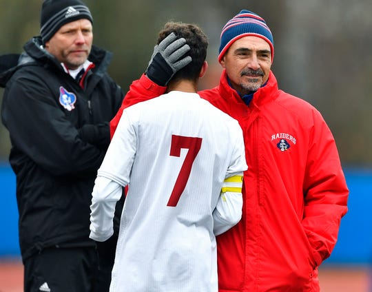 Fairport head coach Gianni Bussani, right, hugs Jude Rouhana as he comes off the field late in the NYSPHSAA Boys Soccer Class AA final in Middletown on Sunday morning. Fairport's season ended with a 4-0 loss to Brentwood-XI.