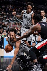 San Antonio Spurs' Derrick White, left, falls after colliding with Portland Trail Blazers' Nassir Little during the first half of an NBA basketball game, Saturday, Nov. 16, 2019, in San Antonio.