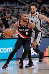 Portland Trail Blazers' Damian Lillard (0) evades San Antonio Spurs' Derrick White during the first half of an NBA basketball game, Saturday, Nov. 16, 2019, in San Antonio.