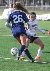 Shoreham-Wading River's Lydia Radonavitch attempts to dribble past Spencerport's Amy Cannan in the NYSPHSAA Class A girls soccer championship game at SUNY Cortland on Sunday, Nov. 17, 2019.