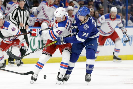 Tampa Bay Lightning center Anthony Cirelli (71) knocks the puck away from New York Rangers center Lias Andersson (28) during the third period of an NHL hockey game Thursday, Nov. 14, 2019, in Tampa, Fla. (AP Photo/Chris O'Meara)
