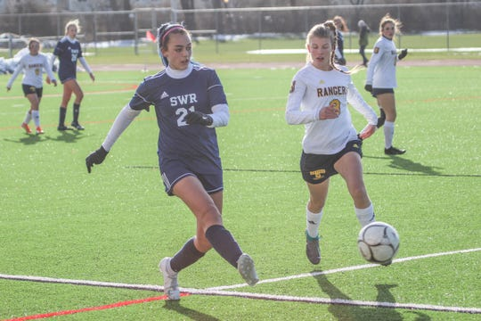 Shoreham-Wading River's Elizabeth Shields sends a pass before Spencerport's Erica Beaty closes in during the NYSPHSAA Class A girls soccer championship game at SUNY Cortland on Sunday, Nov. 17, 2019.