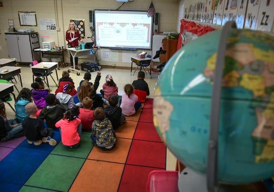 Kristin Harrington, first grade teacher in her first year at Nevitt Forest Elementary School reads to her children in Anderson Monday.