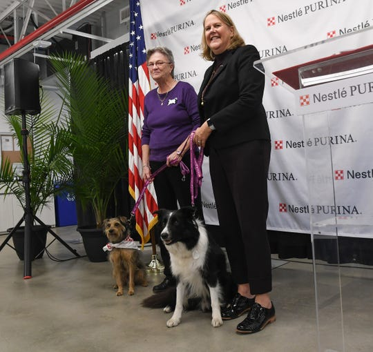 Dr. Katherine Reusing, left, Northeast Council in Domestic Violence accepts a purple leash from Nina Leigh Krueger, Purina Presidentduring the grand opening of the Purina Hartwell plant in Hartwell, Georgia Monday, November 18, 2019. Purina gave $20,000 to the pet-friendly domestic violence shelter from its Purple Leash Project with Red Rover, part of the opening at the plant.