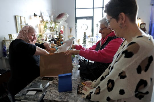 Owner Tarina Swanson, left, bags purchased items for Jeanne Ross and her daughter Amy Van Effen, right, at Sapphire Moon Chocolates in Grand Chute.