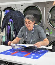 Nancy Sanchez folds a T-shirt at Wash This Way at 710 Butternut St. for a wash-and-fold laundry services customer on Monday, Nov. 18, 2019.
