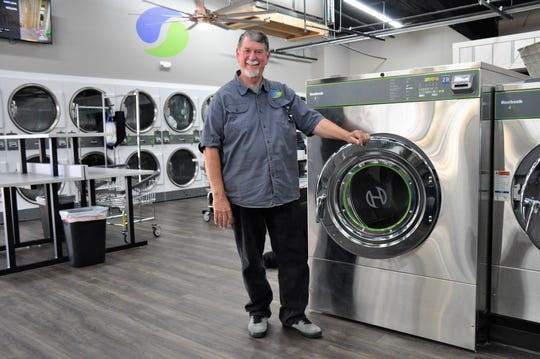 Mike Reppart, co-owner of Wash This Way, stands next to one of the large washing machines Monday, Nov. 18, 2019, at the 710 Butternut St. location that opened in late May.