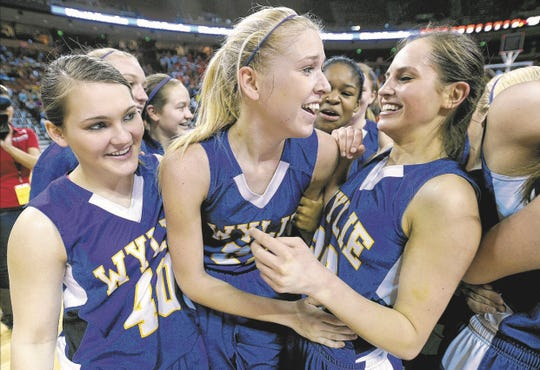 Wylie players Shelby Tucker (from left); Peyton Little, named the state tournament's MVP; and Bailey Turner celebrate after the Lady Bulldogs won their second straight Class 3A state title with a win over Celina in Austin on Saturday.