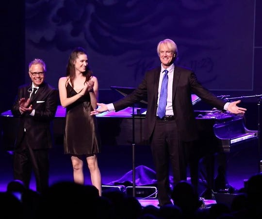 John Tesh on stage with Mark Fisher and his daughter, Prima.