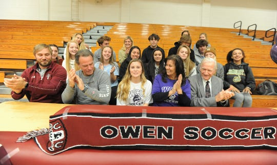 Family, teammates and coaches join Mikayla Roseman in the gym at Owen High School on Nov. 13, when she signed to play soccer for the Western Carolina University Catamounts.