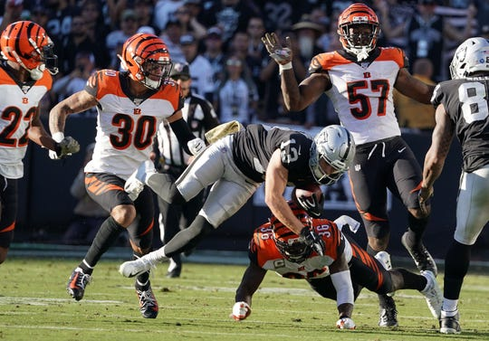 Nov 17, 2019; Oakland, CA, USA; Oakland Raiders wide receiver Hunter Renfrow (13) is pursued by Cincinnati Bengals cornerback William Jackson (22), free safety Jessie Bates (30), linebacker Germaine Pratt (57) and strong safety Shawn Williams (36) in the third quarter at Oakland-Alameda County Coliseum. The Raiders defeated the Bengals 17-10.