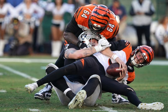 Nov 17, 2019; Oakland, CA, USA; Cincinnati Bengals quarterback Ryan Finley (5) is sacked by Oakland Raiders defensive end Maxx Crosby (98) after getting past Cincinnati Bengals offensive tackle John Jerry (64) during the fourth quarter at Oakland Coliseum.