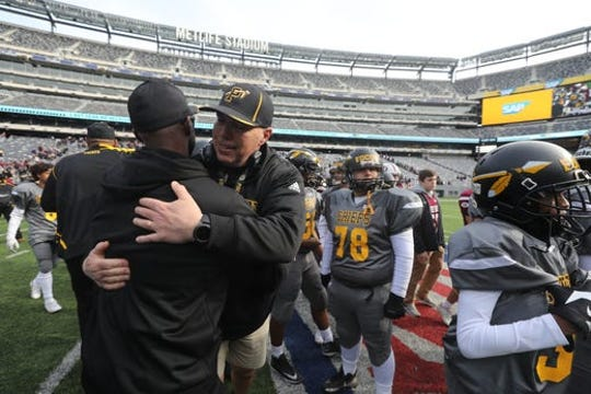 Dan Higgins hugs an assistant coach following Piscataway's bowl championship at MetLife Stadium last season