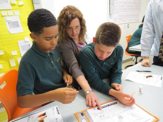 Mackias Ysaac of Fords and Ryan Bokina of Scotch Plains examine the evidence during their weeklong CSI program under the guidance of science teacher Andrea Barnett.