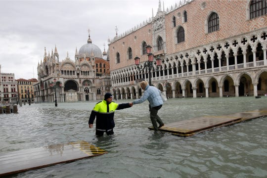 A city worker helps a woman who decided to cross St. Mark square on a gangway, in spite of prohibition, in Venice, Italy on Sunday.