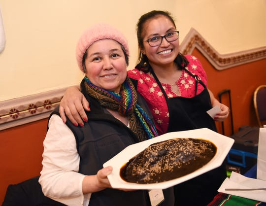 Aida Villa of Detroit, left, with her sister, Araceli Villa, displays her second place winner Mole Poblano. Traditional Mexican mole is a sauce made with chili peppers, tomatoes and other ingredients, was the star at the Holy Mole! contest at El Kiosko in Detroit on Sunday.