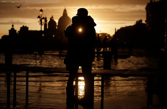 A couple stands in a golden sunset in Venice on Sunday, just hours after an exceptional 1.5 meter tide receded from nearby St. Mark's Square