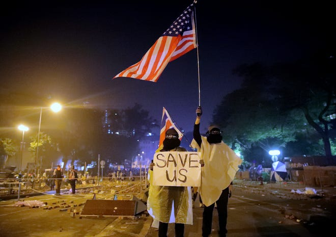 """Protesters hold British and American flags and a sign reading """"Save Us"""" as they stand near Hong Kong Polytechnic University after police gave protestors an ultimatum to leave the campus in Hong Kong, early Monday, Nov. 18, 2019."""