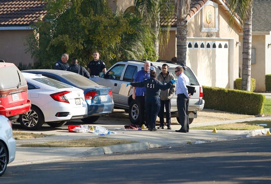 Fresno police investigators work on the scene where a shooting took place at a house party which involved multiple fatalities and injuries in Fresno, Calif., Monday, Nov. 18, 2019.