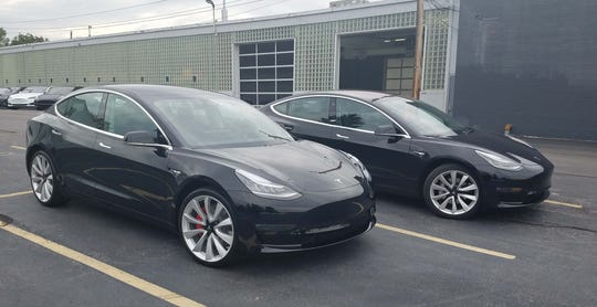 Tell the difference? The external differences between Henry Payne's RWD Tesla Model 3, right, and the new Tesla Model 3 Performance are subtle. The Performance model gets bigger Brembo brakes with red calipers — and an underlined, dual motor badge in the rear.
