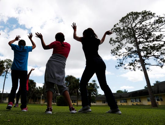 Girls dance on Sept. 24 as they do exercises at a shelter for migrant teenage girls in Lake Worth, Fla.