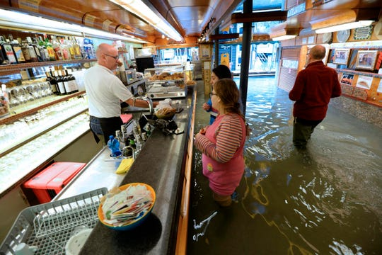 Venetian people in a bar amid rising water in Venice, northern Italy, Sunday, Nov. 17, 2019.