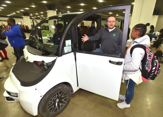 May Mobility Field Autonomy Engineer Jared Miles, left, of Ypsilanti, talks to Jasmine Horton, 13, of Pittsburgh, about the Ann Arbor based start up self driving shuttle service vehicle during a March 30, 2019 convention of the National Society of Black Engineers at Cobo Center in Detroit.