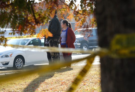 Yia Lee watches police investigate her neighbor's house on Lamona Ave. where a shooting took place at a house party.
