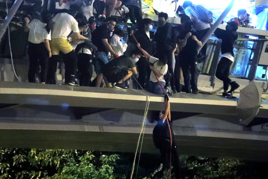 Protestors use a rope to lower themselves from a pedestrian bridge to waiting motorbikes in order to escape from Hong Kong Polytechnic University and the police in Hong Kong, Monday, Nov. 18, 2019.