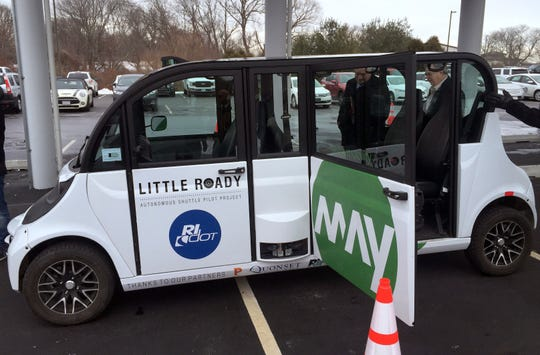 People view a new self-driving shuttle, one of a fleet of vehicles unveiled by Ann Arbor startup May Mobility at the Quonset Business Park in R.I. on  Feb. 20, 2019.